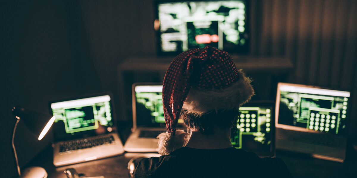 Computer hacker wearing santa hat while working on laptop late at night