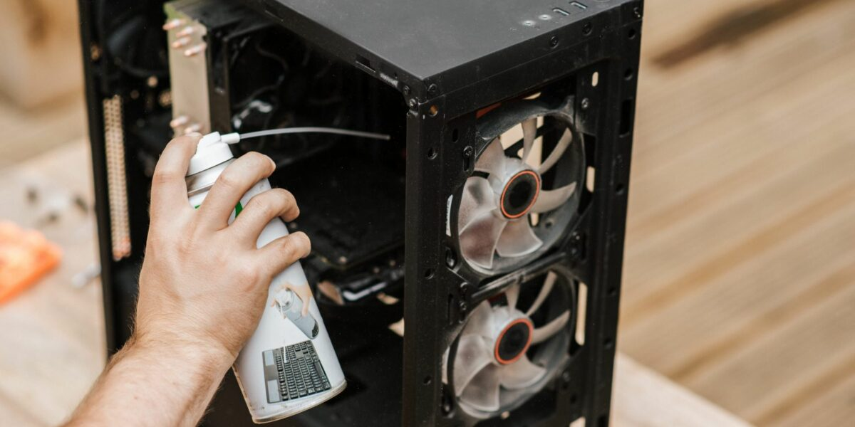 A user is cleaning the PC fans of their computer with a compressed air can.