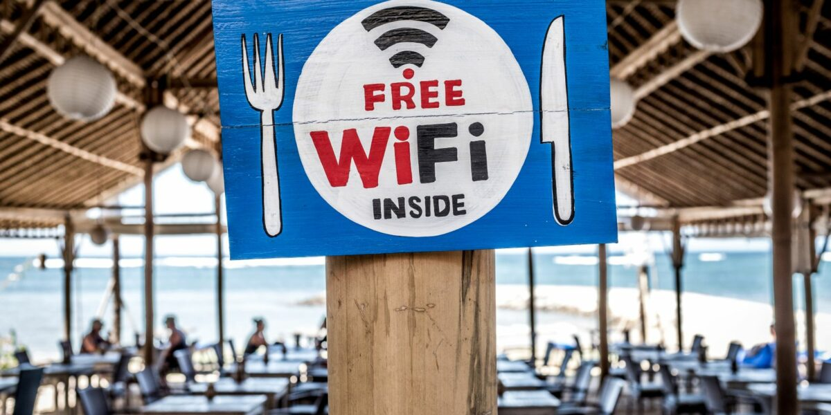 a painted sign on a pillar in a beach restaurants advertising free public Wi-Fi inside.