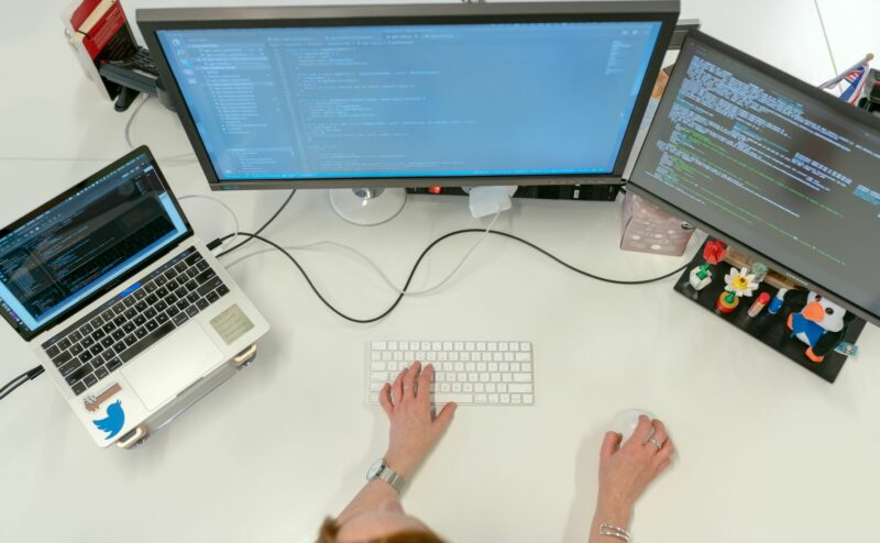 An IT worker setting up synchronization between two desktop and one laptop for a company's data recovery plan.