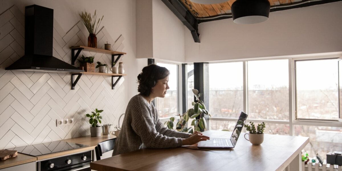 A remote working work from home in their rustic kitchen.